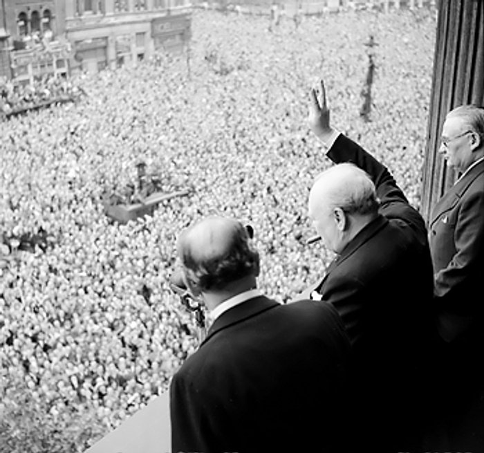 World War II in Europe is over- Prime Minister Winston Churchill waves to celebratory London crowds